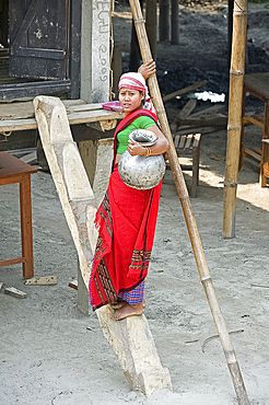Assamese tribal village woman with water pot, climbing simple wooden steps up to her house, Majuli Island, Assam, India