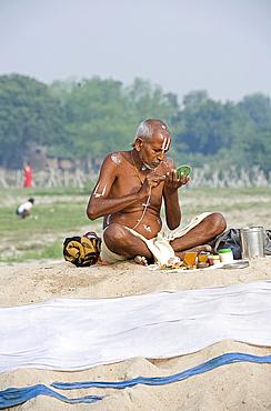 Vishnaivite holy man sitting cross legged, preparing for morning puja, applying sandalwood tilaks on forehead and arms, wearing simple white dhoti and sacred Hindu string, Patna, Bihar, India, Asia