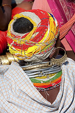 Head of Bonda tribeswoman wearing traditional beaded cap held with metal clips, large earrings and metal and bead necklaces, Rayagader, Orissa, India, Asia