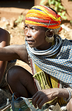 Bonda tribeswoman in traditional dress with beaded cap, large earrings and metal necklaces selling vegetables at weekly market, Rayagader, Orissa, India, Asia