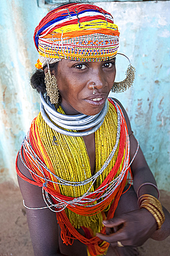 Bonda tribeswoman wearing traditional bead costume with beaded cap, large earrings and metal necklaces at weekly market, Rayagader, Orissa, India, Asia