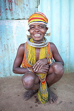 Bonda tribeswoman, smiling, wearing traditional bead costume with beaded cap, earrings and metal necklaces at weekly market, Rayagader, Orissa, India, Asia
