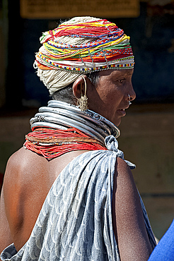 Bonda tribeswoman wearing grey blue cotton shawl and beads with beaded cap, large earrings and metal necklaces at weekly market, Rayagader, Orissa, India, Asia