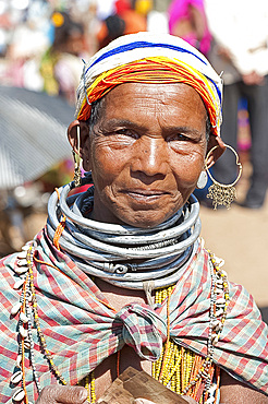 Smiling Bonda tribeswoman wearing cotton shawl over traditional bead costume, beaded cap, large earrings and metal necklaces, Rayagader, Orissa, India, Asia