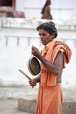 Joranda monk at dusk, wearing orange cloth, sounding a cymbal as preparation for ritual evening prayer, Joranda, Orissa, India, Asia