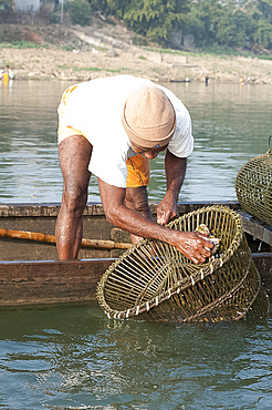 Fisherman in wooden boat, washing his coir and bamboo fishing pots, River Mahanadi, Orissa, India, Asia