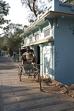 Cycle rickshaw wallah waiting for fare next to a riverside shrine on the banks of the Hooghly River, Serampore, West Bengal, India, Asia