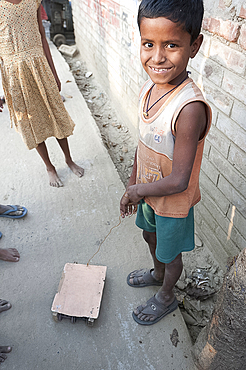 Young smiling village boy with wheeled toy vehicle pulled on piece of wire, in a village street, rural West Bengal, India, Asia
