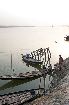 Men at dusk tending small wooden fishing boats on the River Hugli (River Hooghly), West Bengal, India, Asia