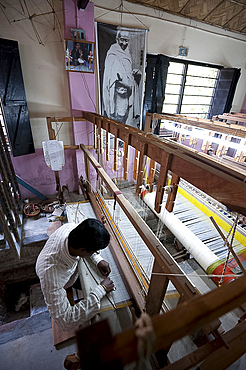 Man working a loom in a village weaving workshop beneath a large picture of Mahatma Gandhi, Kalna, West Bengal, India, Asia