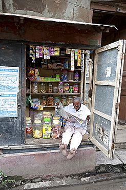 Shop owner reading the newspaper in the morning, Kolkata, West Bengal, India, Asia
