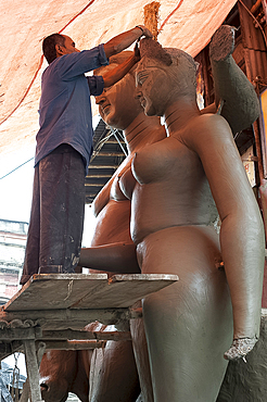 Sculptor working on large moulded clay deity from the River Hugli, Kumartuli district, Kolkata, West Bengal, India, Asia