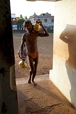 Monk, follower of Mahima Dharma sect, wearing orange loincloth carrying brass pots of water into the temple at sunset, Joranda, Orissa, India, Asia