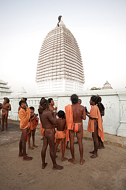 Joranda monks gathered in front of temple, vimula visible above them, after prayers at dusk, Joranda, Dhenkanal, Orissa, India, Asia