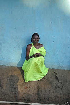 Woman sitting in late afternoon sunshine against blue house wall in Mali tribal village, Jeypore district, Orissa, India, Asia