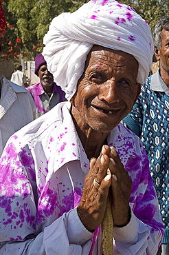 Man offering Namaste greeting on his way back from village wedding celebrations where watered pink dyed powder has been thrown, Ajmer district, Rajasthan, India, Asia