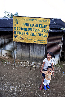 Naga village children beneath a local government sign for livelihood improvement through sustainable farming, rural Nagaland, India, Asia