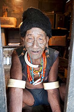 Naga Konyak tribal headhunter with traditional tattooed face, deer horn earrings, animal teeth and beads and elephant tusk armbands, Ngangting, Nagaland, India, Asia