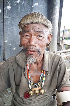 Naga Konyak tribal head hunter with traditional headhunter necklace with brass heads, bamboo earrings, elephant tusk armbands, Ngangting, Nagaland, India, Asia