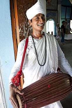 Gayan (musician) dressed in white cotton, with horizontal khol drum at the Uttar Kamalabari Hindu monastery, Majuli Island, Assam, India, Asia
