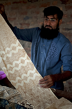 Muslim man showing hand block printed fabric using natural dye made from plants and roots, Bhuj district, Gujarat, India, Asia