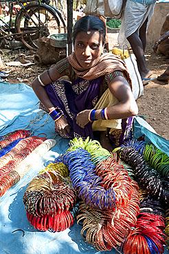 Young woman with ropes of coloured bangles for sale in Mali weekly tribal market, Guneipada, Koraput district, Orissa (Odisha), India, Asia