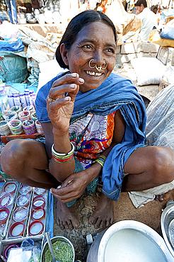 Smiling Mali tribeswoman with gold noserings selling yoghourt in Mali weekly tribal market, Guneipada, Orissa (Odisha), India, Asia