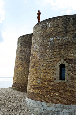 Antony Gormley's sculpture of a man looking out to sea, standing on the Napoleonic Martello tower in Aldeburgh, Suffolk, England, United Kingdom, Europe