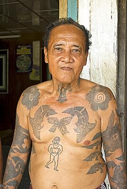 Jugah, an Iban tribal longhouse head man (Tuai Rumah), with traditional warrior tattoos, Kapit district, Sarawak, Malaysian Borneo, Malaysia, Southeast Asia, Asia