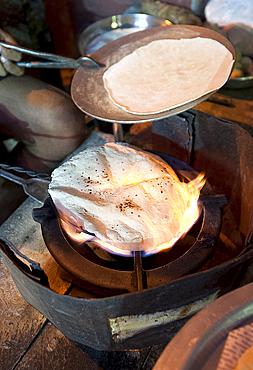 Street chapati maker, making bread over a naked flame using traditional basic equipment, Puri, Odisha, India, Asia