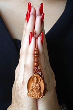Buddhist woman praying with a wood Buddha pendant in hands, Ho Chi Minh City, Vietnam, Indochina, Southeast Asia, Asia