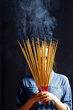 Young Chinese woman praying with big burning incense sticks in her hands, Ha Chuong Hoi Quan Pagoda, Ho Chi Minh City, Vietnam, Indochina, Southeast Asia, Asia