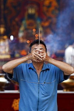 Chinese man burning incense and praying to a prosperous future, Guan Di Chinese Taoist Temple, Kuala Lumpur, Malaysia, Southeast Asia, Asia