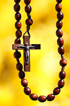 Wooden rosary against yellow broom flowers, France, Europe