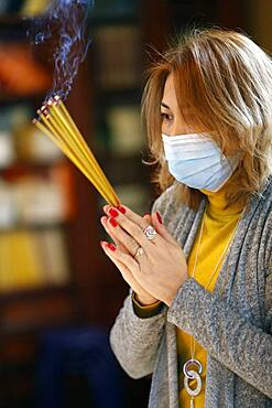 Woman wearing surgical mask praying with incense sticks, Tu An Buddhist Temple, Haute Savoie, France, Europe
