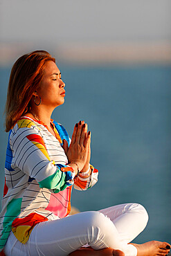 Woman practising yoga meditation by the sea before sunset as concept for silence and relaxation, United Arab Emirates, Middle East