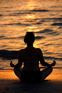 Woman practising yoga meditation on beach at sunset as concept for silence and relaxation, United Arab Emirates, Middle East