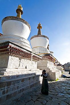Pilgrim in front of the white stupas at the Tashilumpo monastery, Shigatse, Tibet Autonomous Region, China, Asia