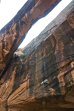 Woman rapelling down a giant arch, canyoneering, Moab, Utah, United States of America, North America