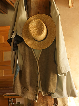 Old straw hat and vest hanging on a wooden post, Upper Canada Village, Morrisburg, Ontario, Canada, North America