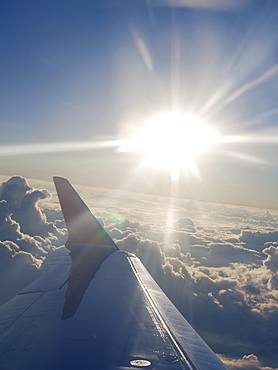 Airplane wing and sun burst over clouds while in flight en route to Houston, Texas, United States of America, North America