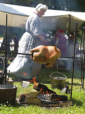 French-Indian War reenactment, woman cooking a turkey over an open fire, Fort Niagara, Youngstown, New York State, United States of America, North America