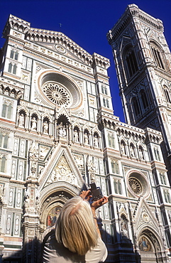 Woman taking a photo of the Cathedral of Santa Maria del Fiore (The Duomo), Piazza del Duomo, Florence, Tuscany, Italy, Europe