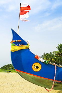 Colourful fishing boat with Indian flag and golden eye motifs on Marari Beach, Mararikulam, Alappuzha (Alleppey), Kerala, India, Asia
