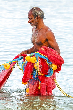 Fisherman retrieving large net to shore at popular Marari Beach, Mararikulam, Alappuzha (Alleppey), Kerala, India, Asia