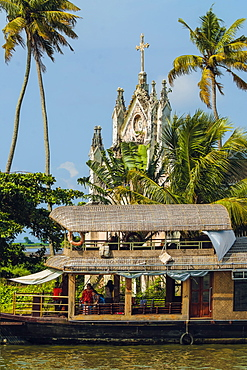Old church with patinated facade and moored houseboat on a backwaters cruise visitor stop, Alappuzha (Alleppey), Kerala, India, Asia