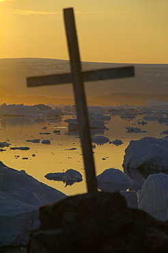 Cross in front of sunset over icebergs Paarnakajiit Sermilik Fjord Eastgreenland