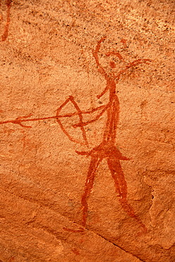Neolithic rock drawing of a human with bow and arrow and an animals head Acacus Libya