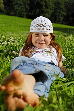 Girl lies barfoot in a meadow