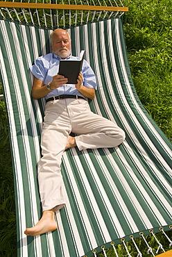 Elderly gentleman lying in a hammock reading a book